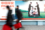 Pedestrians walk past a Ping An Insurance Group's advertisement in Shanghai, China on 12 January 2010.  Ping An is one of the largest insurers in the world, topped only by China's government owned national insurer.