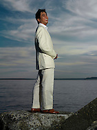 Asian man in suit stands in front of a large body of water.