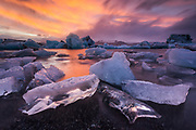 February 08 – Stunning morning at Jökulsárlón glacier lagoon, fresh blue icebergs are a great contrast to the orange sunrise colors. <br /> <br /> <br /> Glacier Lagoon, Iceland