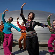 Dancers perform in front of the new National Theatre in Beijing, which is getting ready to host the 2008 Olympics.