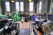 Nederland, Appeltern, 18-8-2019 Het historische gemaal, stoomgemaal de Tuut . In 1917 was besloten tot de bouw, aan de toenmalige Maasdijk nabij de Tuut, de uitmonding van de Nieuwe Wetering in de Maas, van het Stoomgemaal De Tuut te Appeltern. Het stoomgemaal is in 1918 in gebruik genomen en in 1919 definitief opgeleverd. Het gemaal is gebouwd in opdracht van de samenwerkende waterschappen in Maas en Waal en het Rijk van Nijmegen . Tegenwoordig is het niet meer als actief gemaal in gebruik, maar kan in noodgevallen wel worden ingezet. vrijwilligers houden het machinepark en stookovens in goede conditie. Een mooi voorbeeld van industrieel erfgoed .FOTO: FLIP FRANSSEN