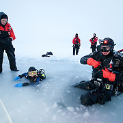 Shawn Harper emerges from the dive hole cut in the Arctic Ocean.