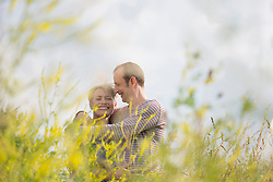 Mature couple embracing each other in field, smiling