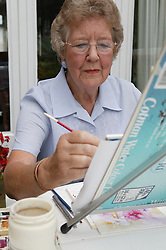 Elderly woman painting in watercolours,
