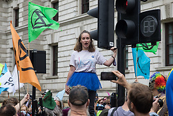 London, UK. 3rd September, 2020. A young climate activist addresses fellow Extinction Rebellion activists at a 'Carnival of Corruption' protest outside the Treasury against the government's facilitation and funding of the fossil fuel industry. Extinction Rebellion activists are attending a series of September Rebellion protests around the UK to call on politicians to back the Climate and Ecological Emergency Bill (CEE Bill) which requires, among other measures, a serious plan to deal with the UK's share of emissions and to halt critical rises in global temperatures and for ordinary people to be involved in future environmental planning by means of a Citizens' Assembly.