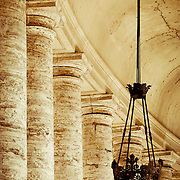Columns and an ornate light in the outdoor corridor surrounding St. Peter's Square in the Vatican. (Rome, Italy)<br />