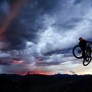 Andrew Whiteford gets air while riding Teton Singletrack as a summer thunderstorm highlights sunset.