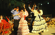 """Women dancing flamenco and wearing traditional dress frilly flamenco dresses during the Feria..The Feria de abril de Sevilla, """"Seville April Fair"""" dates back to 1847. During the 1920s, the feria reached its peak and became the spectacle that it is today. It is held in the Andalusian capital of Seville in Spain. The fair generally begins two weeks after the Semana Santa, Easter Holy Week. The fair officially begins at midnight on Monday, and runs six days, ending on the following Sunday. Each day the fiesta begins with the parade of carriages and riders, at midday, carrying Seville's citizens to the bullring, La Real Maestranza...For the duration of the fair, the fairgrounds and a vast area on the far bank of the Guadalquivir River are covered in rows of casetas (individual decorated marquee tents which are temporarily built on the fairground). Some of these casetas belong to the prominent families of Seville, some to groups of friends, clubs, trade associations or political parties. From around nine at night until six or seven the following morning, at first in the streets and later only within each caseta, crowds of people party and dance Sevillanas, traditional Flamenco dances, Sevillan style drinking Jerez sherry, or Manzanilla wine, and eating tapas. Men and women dress up in their finery, the traditional """"traje corto"""" (short jacket, tight trousers and boots) for men and the """"faralaes"""" or """"trajes de flamenca"""" (flamenco style dress) for women. The men traditionally wear hats called """"cordobés""""."""