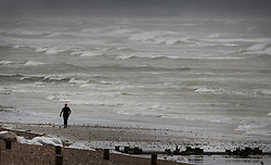 © Licensed to London News Pictures. 19/11/2016. Lancing, UK. A walker braves the wind and waves of Storm Angus as she walks on the beach at Lancing. The south east has experienced winds of up to 80 miles per hour as the first named storm of the season hits. Photo credit: Peter Macdiarmid/LNP