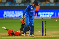 September 18, 2018 - Dubai, United Arab Emirates - Hong Kong cricket captain Anshuman Rath dives in to the crease to complete a run while Indian wicketkeeper MS Dhoni looks on as bails fly during the 4th cricket match of Asia Cup 2018 between India and Hong Kong at Dubai International cricket stadium,Dubai, United Arab Emirates. 09-18-2018  (Credit Image: © Tharaka Basnayaka/NurPhoto/ZUMA Press)