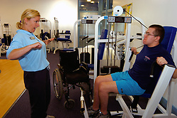 Disabled man in wheelchair using new gym facilities especially adapted for disabled access to keep fit & healthy Yorkshire UK