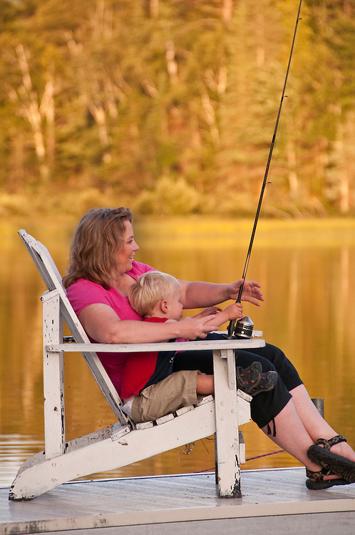 A young boy and his mother fish the Michigamme River at the Republic Island Cottage near Republic Michigan.