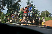 """Women and children ride in the back of a """"bush taxi"""" on the way to Kattin from Bangui. These bush taxis, along with pick-up trucks and big lorries, are considered public transportation, and are usually overloaded with luggage and people, causing frequent breakdowns, flat tires, and accidents."""