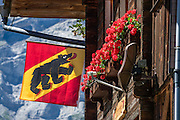 The square Bern canton flag has a diagonal bear in a yellow stripe flanked with red triangles. Gimmelwald, Lauterbrunnen Valley, in Bern canton, Switzerland, Europe.