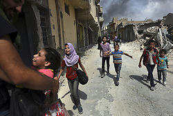 July 2, 2017 - Mosul, Iraq - Civilians, many injured and weak, flee continued battle with ISIS in West Mosul amid ruins of the city. (Credit Image: © Carol Guzy via ZUMA Wire)