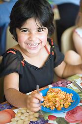 Nursery school girl enjoying her dinner,