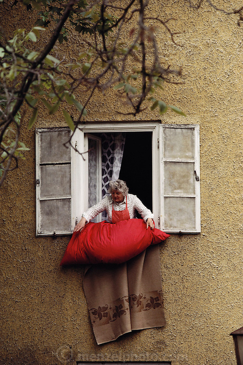 A gray haired woman airs bedding by hanging it out of a window in Weilheim, Bavaria, Germany.