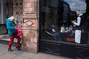 Woman reaches into her bag outside a classy cafe on Piccadilly in central London. Seen from the street outside, we see everyday street events, the lady with a knee raised to help balance her bag while she searches for an item. Although probably unseen by the waiter collecting payment from a customer inside the restaurant, we are witness to the world outside.