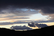 dramatic colorful cloud formations above a silhouette hilly landscape