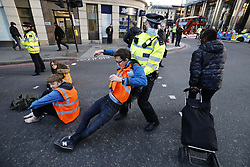 © Licensed to London News Pictures. 25/10/2021. London, UK. Police detain Insulate Britain activists as they block traffic on Bishopsgate in the City of London. The group have restarted their actions to block motorways and major roads causing disruption in the week before the COP26 climate meeting in Glasgow on 31/10/2021. Photo credit: Peter Macdiarmid/LNP