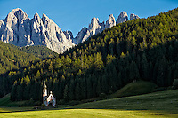 The Dolomites mountain range looms behind the St. Johann Church in St. Magdalena, Italy.
