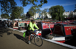 © Licensed to London News Pictures. 04/05/2019. London, UK. A man cycles past Canal boats on the tow path during the Canalway Cavalcade festival in Little Venice, West London on Saturday, May 4th 2019. Inland Waterways Association's annual gathering of canal boats brings around 130 decorated boats together in Little Venice's canals on May bank holiday weekend. Photo credit: Ben Cawthra/LNP