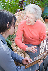 IndependentAge volunteer and older woman looking at an old photo album together,