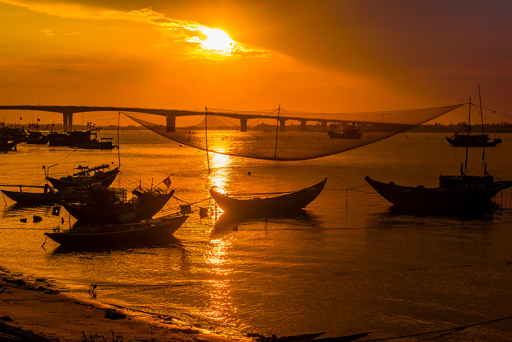 Fishing boats at sunset in the village of Tra Nhieu on the Thu Bon River near Hoi An, Vietnam.