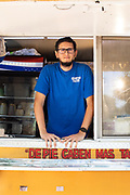 """Luis """"Beto"""" Robledo, owner of Cuantos Tacos, stands inside the window of his taco truck."""