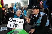 Thousands of Extinction Rebellion activists took over 5 bridges in Central London and blocked them for the day, November 17 2018, Central London, United Kingdom. Lambeth Bridge; a police sergeant tries to convince Lynn Patterson, a Quaker from Bath, to get up. Around 11am people on all bridges sat down in the road and blocked traffic from coming through and stayed till late afternoon. The actvists believe that the government is not doing enough to avoid catastrophic climate change and they demand the government take radical action to save future generations and the planet. Many are willing to be arrested peacefully protesting and up to 80 were arrested on the day. Extinction Rebellion is a grass root climate change group started in 2018 and has gained a huge following of people commited to peaceful protests and who ready to be arrested. Their major concern is that the world is facing catastropohic climate change and they want the British government to act now to save future generations.
