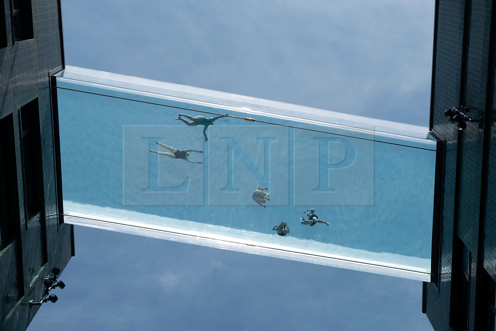 © Licensed to London News Pictures. 02/06/2021. London, UK. Swimmers use the Sky Pool, the worlds first see-through swimming pool as temperatures will reach 27C. The pool is built between the 10th floor of luxury tower blocks in Vauxhall, South London, Holding 400 tonnes of water, the transparent pool is next door to the US Embassy in. London. Photo credit: Ray Tang/LNP
