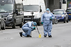 © Licensed to London News Pictures. 24/04/2019. London, UK. A forensic officer takes photographs at the crime scene on Harlesden High Street, Brent in West London where a 21 year old man was stabbed on Tuesday 23 April 2019 at 9.07pm. According to the Met Police, the suspects arrived in two cars before blocking traffic in order to carry out the attack. The victim fled into a bookmakers (Paddy Power) to seek help before the arrival of emergency services. The victim was pronounced dead at a hospital at 2.47am on Wednesday 24 April 2019. Photo credit: Dinendra Haria/LNP