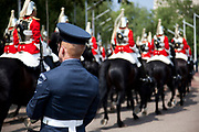 Life Guards pass as a member of the RAF Regiment stands guard. Royal procession for the State Opening of Parliament, London. This procession takes Queen Elizabeth to parliament to deliver the Queen's Speech.