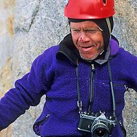 Rick Ridgeway stands with his camera below Rakekniven spire in Queen Maud Land, Antarctica.
