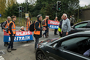 A motorist speaks to Insulate Britain climate activists blocking a slip road from the M25, causing long tailbacks on the motorway, as part of a new campaign intended to push the UK government to make significant legislative change to start lowering emissions on 13th September 2021 in Godstone, United Kingdom. The activists, who wrote to Prime Minister Boris Johnson on 13th August, are demanding that the government immediately promises both to fully fund and ensure the insulation of all social housing in Britain by 2025 and to produce within four months a legally binding national plan to fully fund and ensure the full low-energy and low-carbon whole-house retrofit, with no externalised costs, of all homes in Britain by 2030 as part of a just transition to full decarbonisation of all parts of society and the economy.
