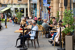 Edinburgh, Scotland, UK. 24 July, 2020. Outdoor cafes on Cockburn Street in the Old Town are busy with customers. Iain Masterton/Alamy Live News