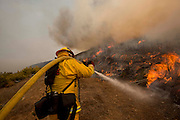 A firefighters extinguishes the wildfire along a hillside in Point Mugu, Calif., Friday, May 3, 2013..(AP Photo/Ringo H.W. Chiu)