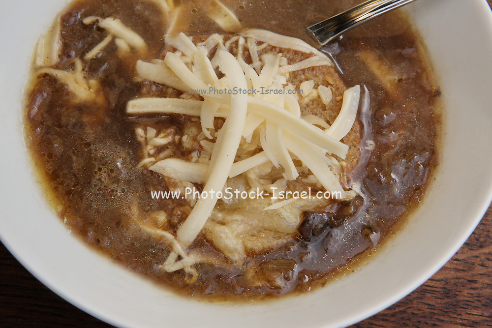 A plate of onion soup with toast and grated cheese