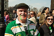 A man with moustache dyed green and orange watching the parade.