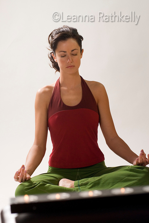 A woman meditates in her home, candles in the forefront.