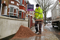 © Licensed to London News Pictures. 09/02/2021. London, UK. A Haringey Council worker spreads the grit over the pavement as snow and freezings temperatures continue in the capital. Photo credit: Dinendra Haria/LNP