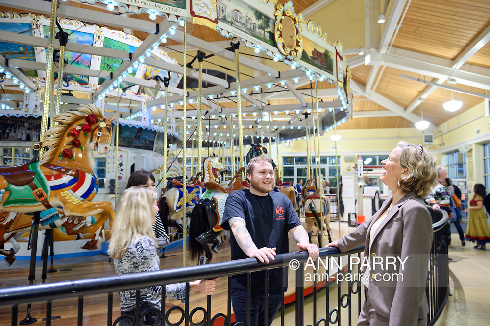 """Garden City, New York, USA. March 9, 2019.  L-R, Carousel operators BETH ORBERG and her son ANDREW OBERGH and Nassau County Executive LAURA CURRAN talk at railing around Nunley's Carousel, during Unveiling Ceremony of mural of a Nunley's Carousel horse. The Obergh family runs the carousel, and raised $85,000 for """"Pennies for Ponies"""" campaign to help restore the horses. Event was held at historic Nunley's Carousel in its Pavilion on Museum Row on Long Island."""