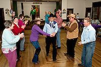 Kristin Durand-Schwarz and Winston Calvon, who celebrated his 90th birthday last week, sashay down the dance floor during the Virginia Reel at the Spring Fling Hoedown dance at Wicwas Grange Hall Saturday evening.  (Karen Bobotas/for the Laconia Daily Sun)
