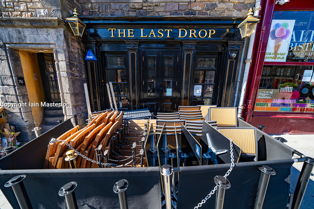 Edinburgh, Scotland, UK. 25 April 2021. Scenes from streets of Edinburgh city centre on Sunday afternoon on the day before non-essential shops and businesses can reopen in Scotland under relaxed covid-19 lockdown rules. Pic. Tables and chairs stacked and ready outside The Last Drop bar in Grassmarket. Iain Masterton/Alamy Live News
