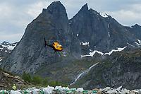 Helicopter carrying stones for work on Reinebringen Sherpa trail construction in Summer 2019, Reine, Moskenesøy, Lofoten Islands, Norway