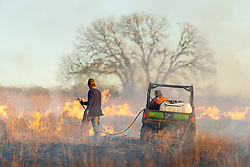 Fire team with ATV and water tank managing fire  during a controlled burn on the Daphne Prairie, a remnant of the Blackland Prairie, Mount Vernon, Texas, USA.
