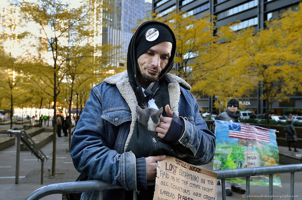 """November 18, 2011, Zuccotti Park, NY. A homeless man who joined the Occupy Wall Street movement begs for money, claiming that he lost his belongings when the police raided the tent camp in the park on November 14, 2011. Photograph awarded and exibited at the """"ewz-Swiss Photo Award 2013""""."""