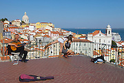 A singer and two young girls at Portas do Sol lookout in Lisbon.