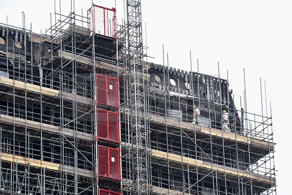© Licensed to London News Pictures. 21/05/2018. LONDON, UK.  Workmen in safety helmets at work behind scaffolding which currently covers the burned out shell of the Grenfell Tower in West London on the day that commemoration hearings begin in the Millennium Gloucester hotel.  Over the next nine days, friends and family will be paying tributes to the 72 victims killed by the fire in the building nearly one year ago.  Photo credit: Stephen Chung/LNP
