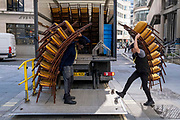 Contractors with the hospitality furniture supplier Well Dressed Tables, load tall stacks of event chairs into the company lorry after a function at Lloyds of London in the City of London, the capitals financial district, on 24th September 2021, in London, England.